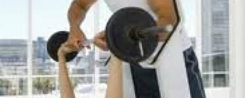 Trainer Spotting Client During Bench Press Exercise