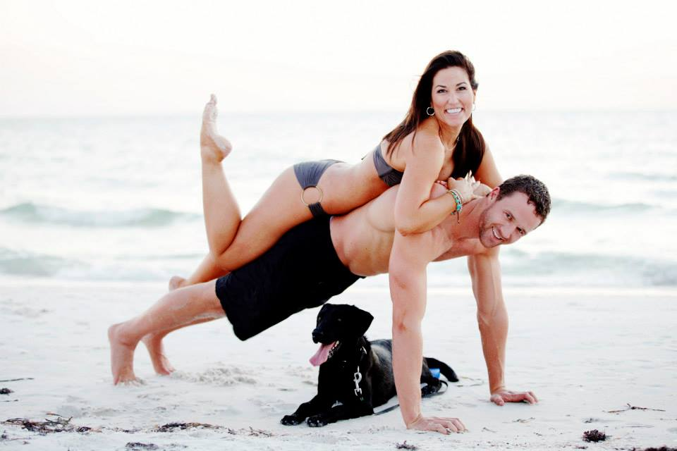 JD doing push-up on beach with wife