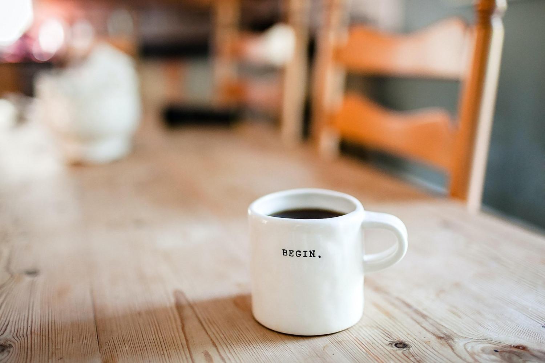 white coffee mug that says begin