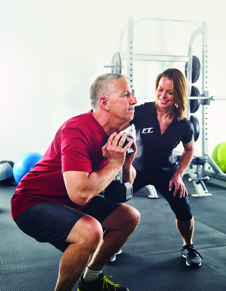 Client squatting with personal trainer