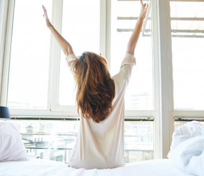 woman sitting and stretching arms in the air in the morning