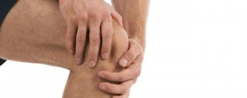 man holding painful knee