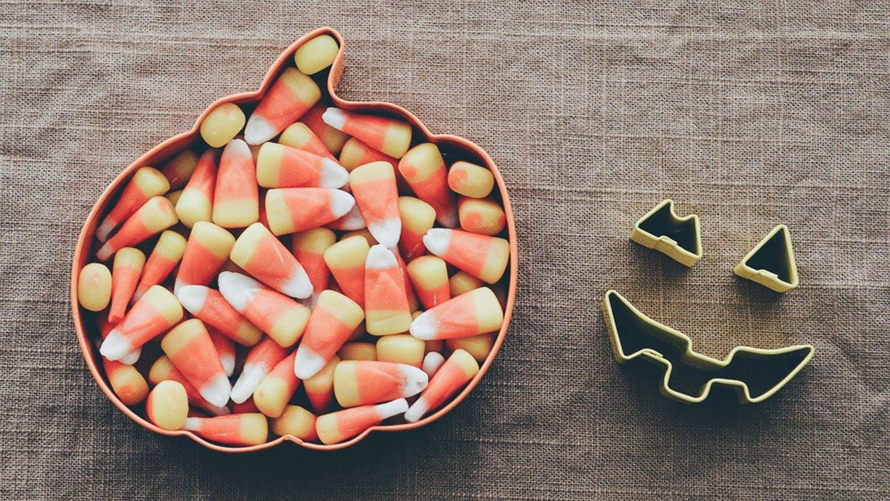 candy corn in a small pumpkin tin