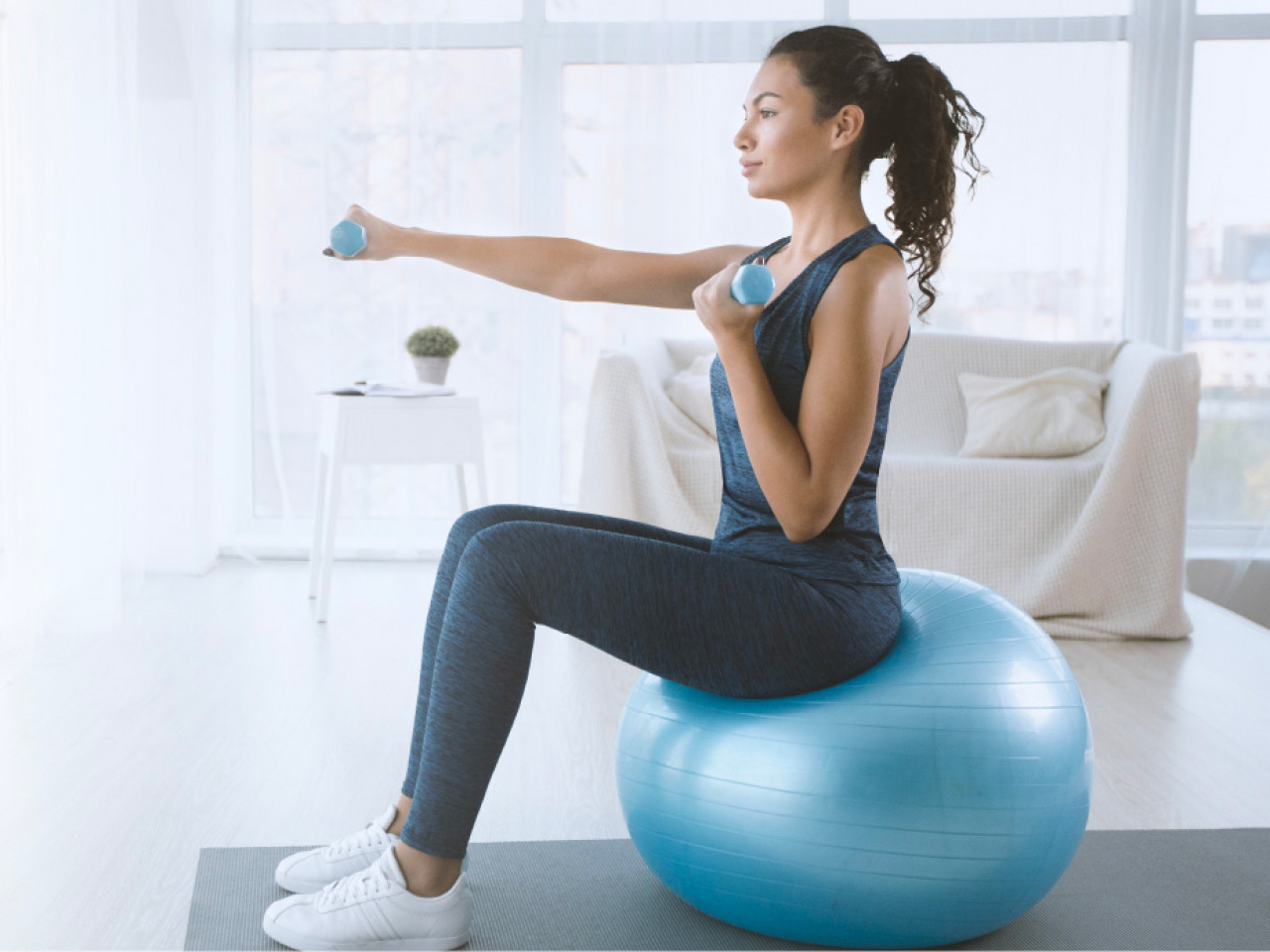 woman using hand weights sitting on an exercise ball