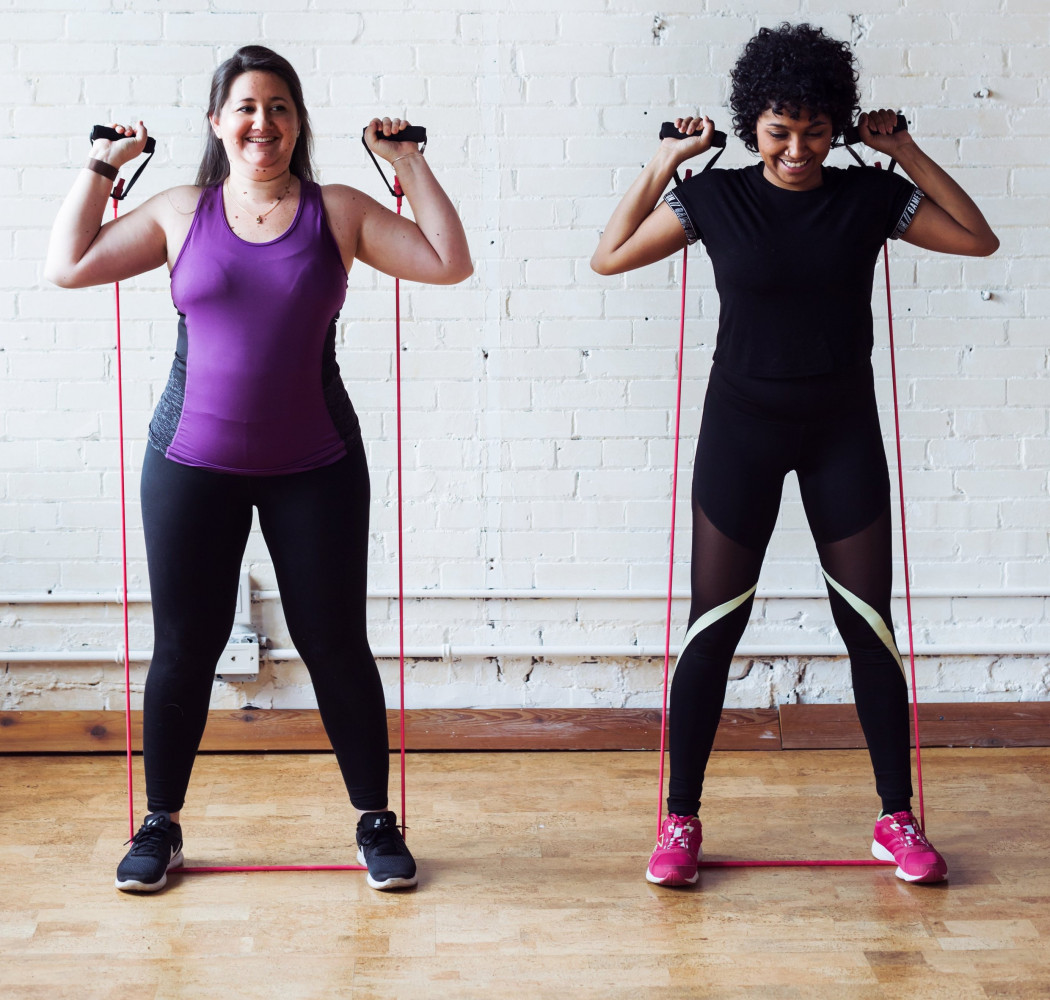two women exercising with bands