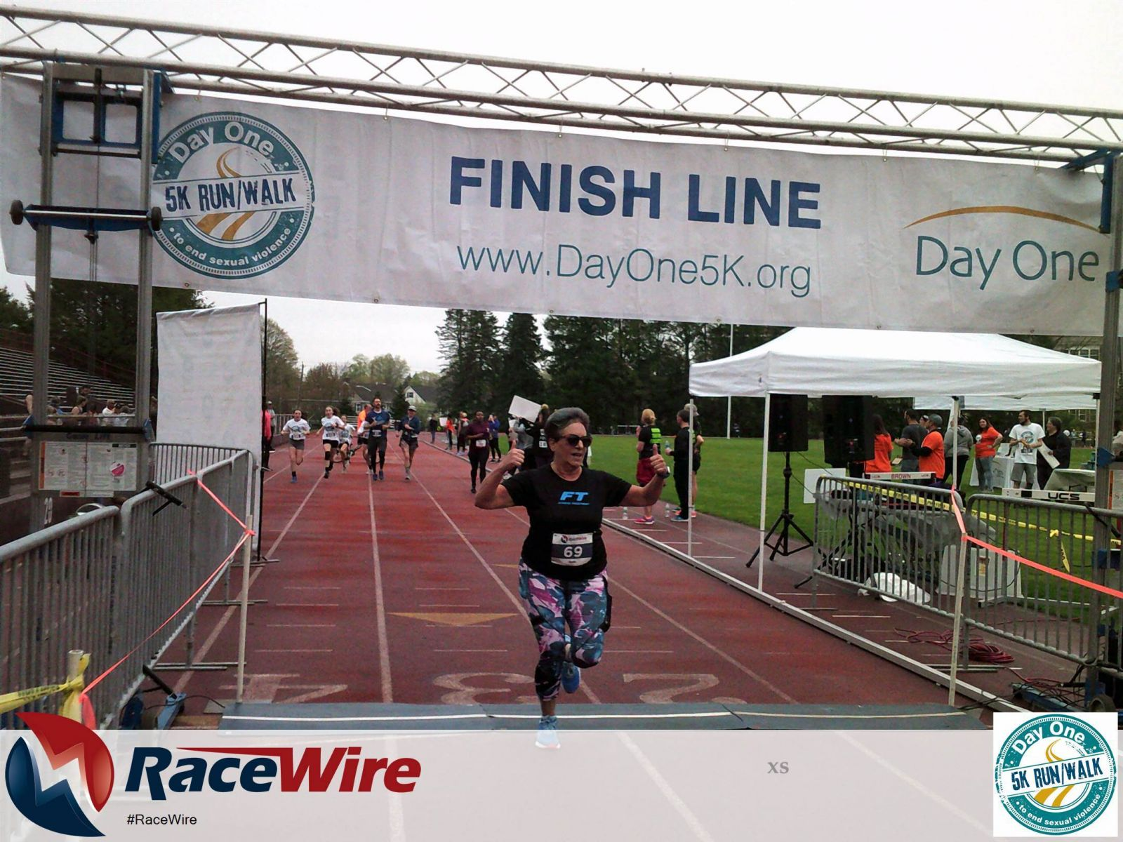 Woman giving thumbs up while crossing finish line