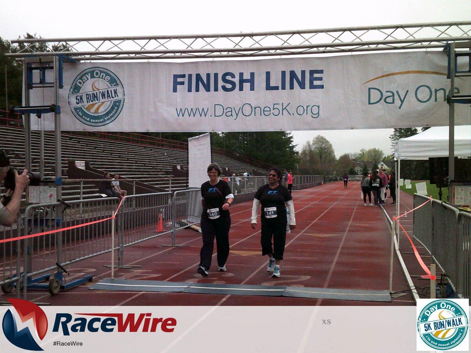 Two women walking across finish line