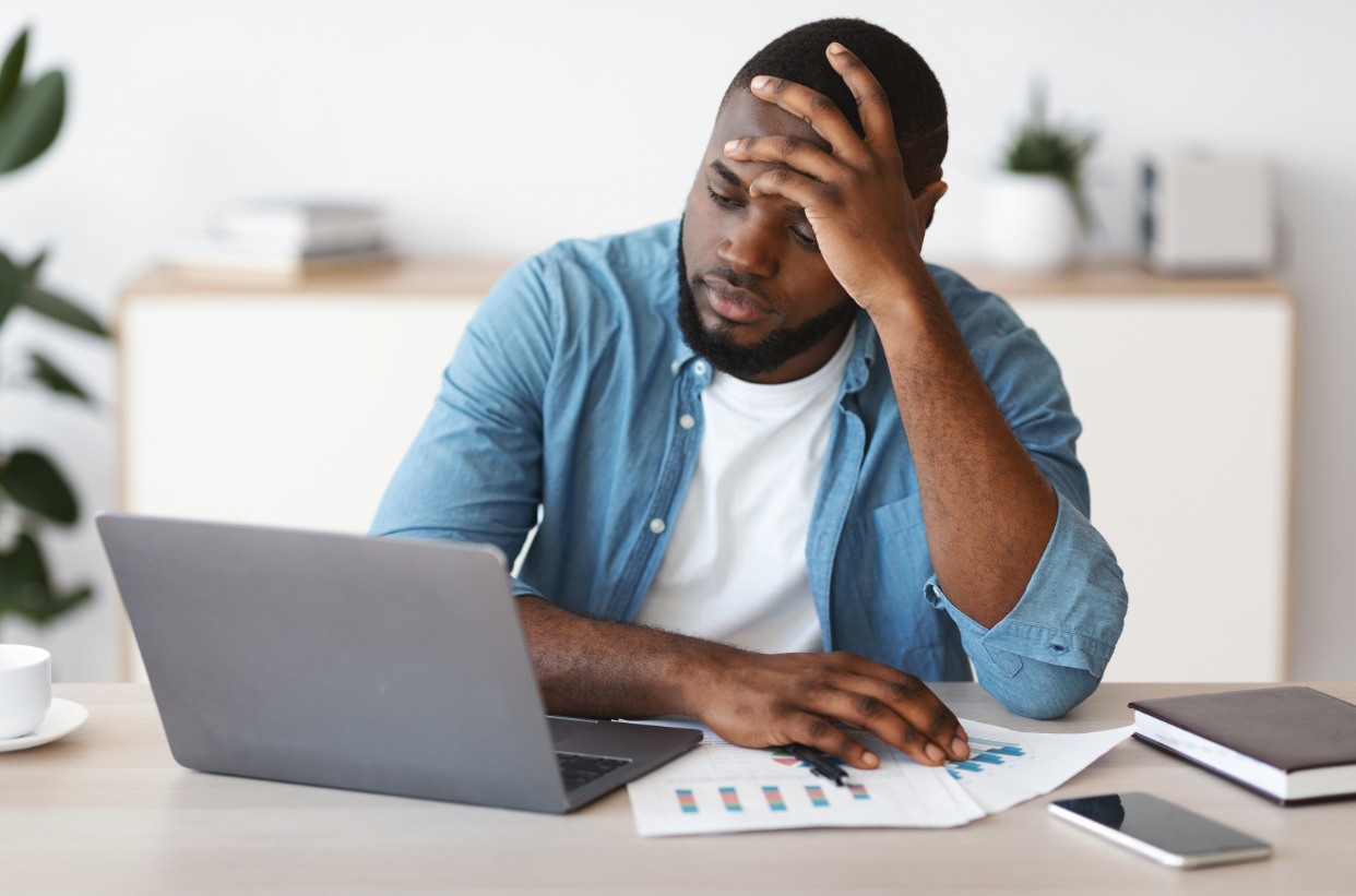 man looking stressed looking at laptop