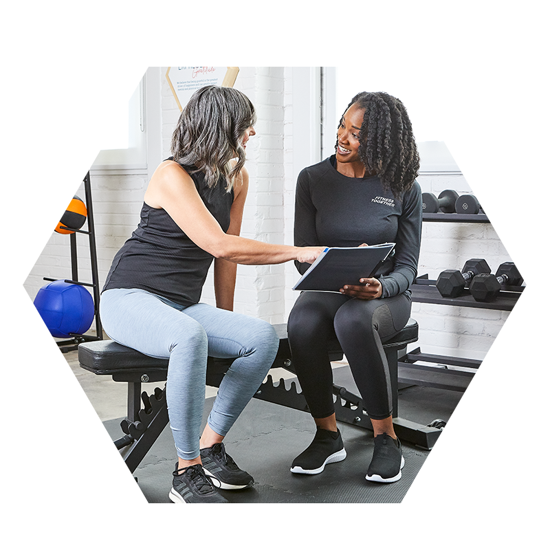 woman sitting with Fitness Together trainer