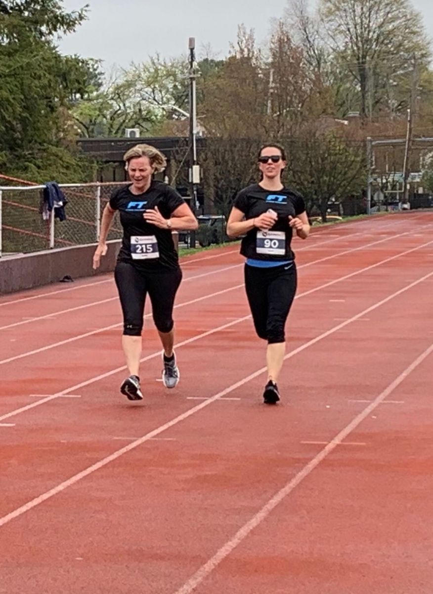 2 Fitness Together runners running 5K on track