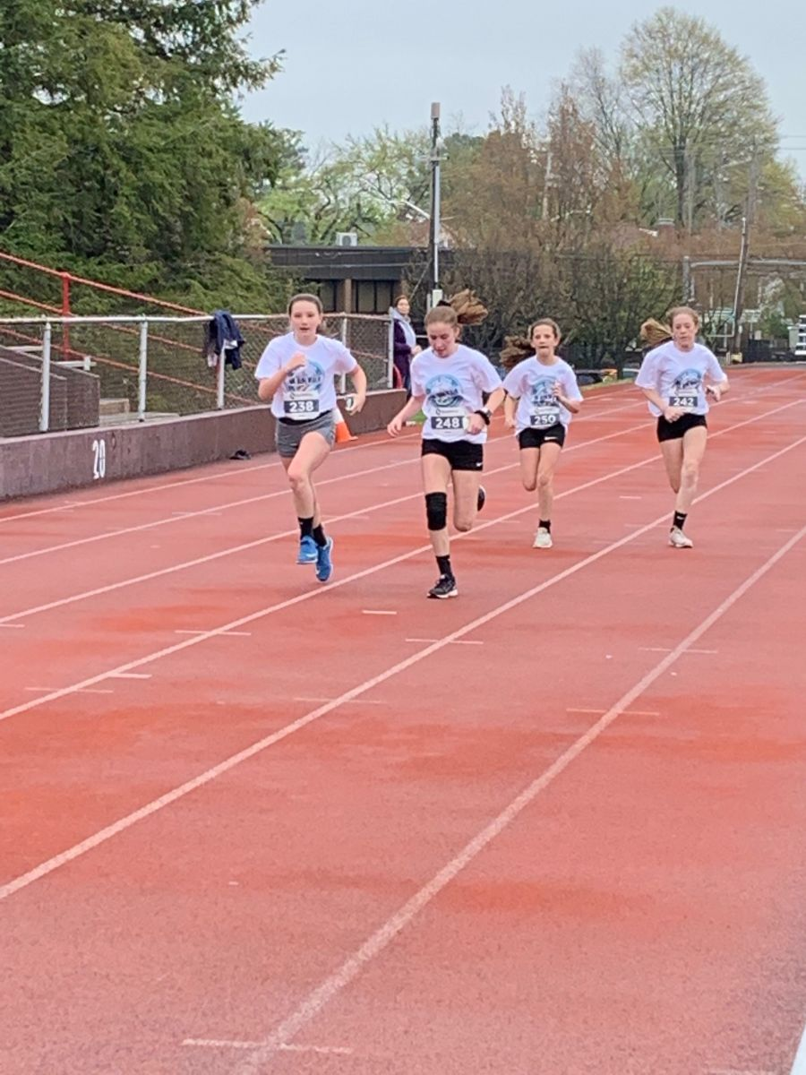 Four teenage girls running on a track