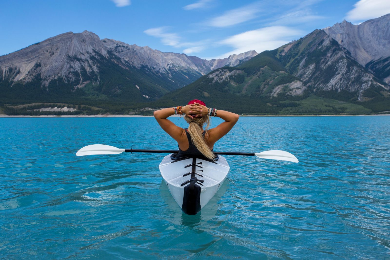 a woman kayaking looking at the mountains